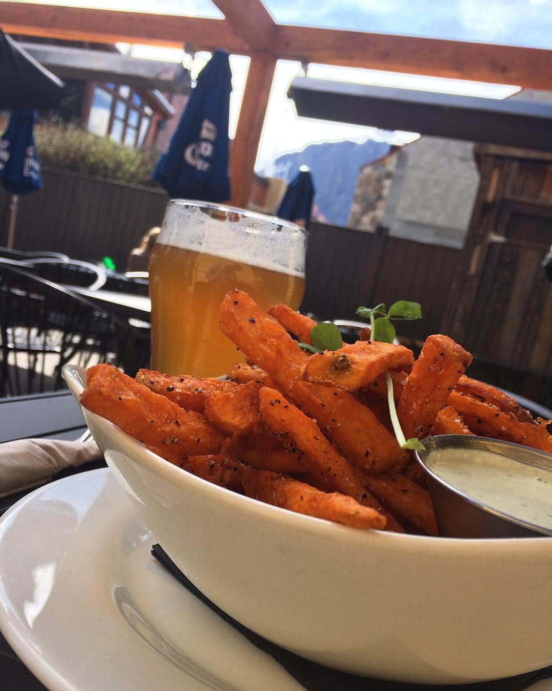 Two of my favourite things: Sweet fries and a crisp pint of @villagebrewery ISA. Nothing better to top off a day in the mountains! Thanks @tavern1883 ❤️ spring patio season! . . . . . #eveningsout #guidemebanff #canmorealberta #localbrews #foodporn #refresh #alfresco #getoutside #goodfood #beer #dinner #aprés #getinmybelly