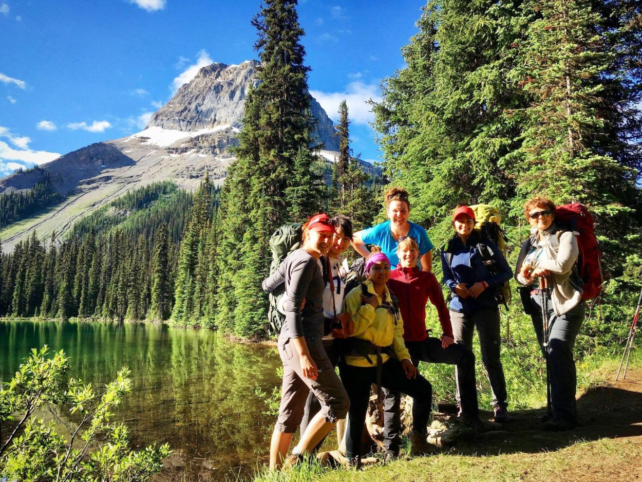 Women backpacking by lake