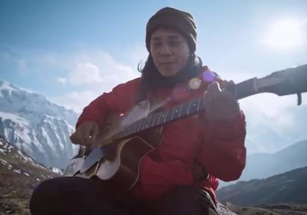 women playing guitar in the mountains
